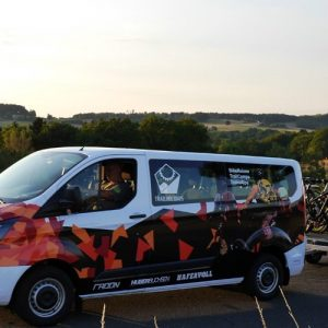 Trailholidays Bike-Shuttlebus mit 9 Sitzen. Ford Transit H1L2 mit Camouflage-dekor. Fahrradanhänger für 10 Mountainbikes für Mountainbike Freeridereisen